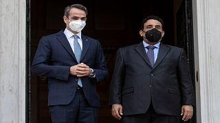 رئيس الوزراء اليوناني كيرياكوس ميتسوتاكيس إلى جانب رئيس المجلس الرئاسي الليبي محمد المنفي