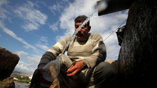 صورة من الارشيف - فلسطيني يملأ زجاجة بالمياه، عند نافورة  بالقرب من مخيم البقعة للاجئين الفلسطينيين في عمان
