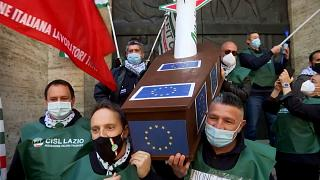 Workers of Alitalia carrying a coffin with a plane inside