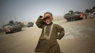 طفل ينظر إلى عربات عسكرية في ضواحي سبين بولداك جنوب شرقي قندهار في أفغانستان. 2009/08/06
