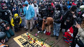Flowers are placed on a banner as demonstrators gather outside the Brooklyn Center Police Department on April 13, 2021, to protest the shooting death of Daunte Wright.