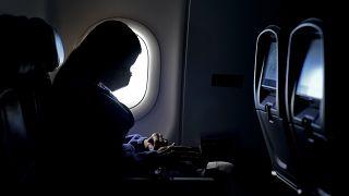 سيدة ترتدي كمامة وتجلس داخل طائرة