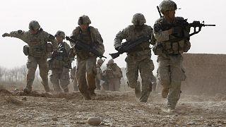 Afganistan'ın Helmand kentinde silahlı grupların açtığı ateşin altında kalan ve  karşılık veren Amerikalı askerler (arşiv)