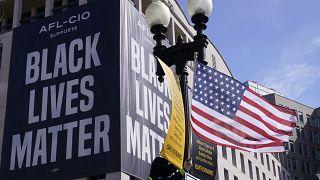 """Un drapeau des États-Unis devant une affiche """"Black Lives Matter"""" à Washington, le 19 mars 2021"""