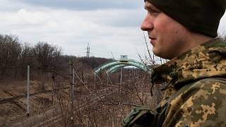 A Ukrainian soldier looks towards the frontline.  The pipes behind him carry water from an area controlled by Kyiv to the area controlled by the Russian-backed separatists