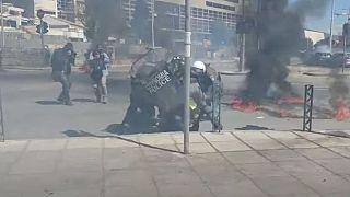 Αστυνομικοί επιχειρούν να σβήσουν φωτιά από μολότοφ σε διαδηλωτή