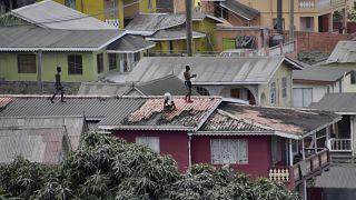 Varias personas limpian la ceniza volcánica del tejado de una casa tras la erupción del volcán La Soufriere, en San Vicente