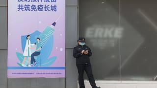"""A worker stands outside a vaccination site with a sign saying """"Timely vaccination to build the Great Wall of Immunity together"""" in Beijing. April 9, 2021."""