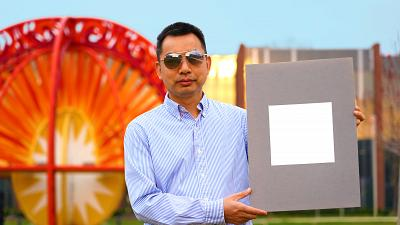 Xiulin Ruan, a Purdue University professor of mechanical engineering, holds up his lab's sample of the whitest paint on record.