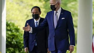President Joe Biden, accompanied by Japanese Prime Minister Yoshihide Suga, walks from the Oval Office to speak at a news conference in the Rose Garden of the White House.
