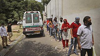 Tesztelésre váró nők és férfiak Új-Delhiben