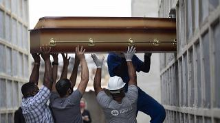 FILE - In this April 13, 2021, file photo, the remains of a woman who died from complications related to COVID-19 are placed into a niche by cemetery workers.