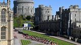 Military personnel in parade dress uniform march past flowers which where placed on the grass for the funeral of Britain's Prince Philip inside Windsor Castle in Windsor.