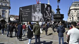 People observe a minute's silence for Britain's Prince Philip at Piccadilly Circus in London.