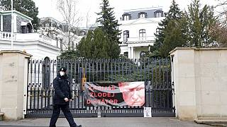 A policeman walks by a poster attached by protesters to a gate of the Russian embassy in Prague, Czech Republic, on Friday
