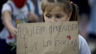 """طفلة ترفع لافتة كتب عليها: """"أريد التعلم في المدرسة""""، وذلك خلال مظاهرة في بيونس ايرس. 2021/04/16"""