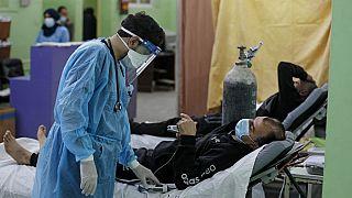 مسعف فلسطيني يعتني بمريض كوفيد -19 في وحدة العناية المركزة في مستشفى الشفاء في غزة، أبريل، 2021