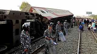 Security forces stand guard as people gather at the site where a passenger train derailed, killing 11 and injuring at least 100 people, near Banha in Egypt