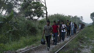 Migrantes caminan por las vías del tren en Palenque, estado de Chiapas, México, el miércoles 10 de febrero de 2021