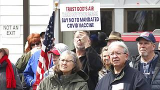 A sign denouncing the COVID-19 vaccine is held up in the crowd gathered at a protest