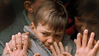 Egy menekültként buszra ültetett kisfiút búcsúztatnak szülei a viszontlátás reményében, Szarajevóban, 1992-ben