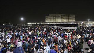 Hunderte Wanderarbeiter warten an einem Busbahnhof auf die Abfahrt in ihre Dörfer, in Neu-Delhi, Indien, Montag, 19. April 2021.