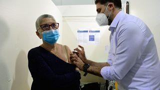 Ein Pfleger verabreicht den Pfizer/BioNTech-Impfstoff an eine Frau in einem Impfzentrum in Marseille.