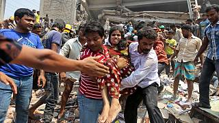 Rescuers assist an injured woman after an eight-story building housing several garment factories collapsed in Savar, near Dhaka, Bangladesh, Wednesday, April 24, 2013