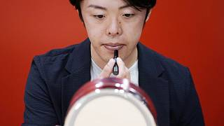 Naruhiko Ito, assistant brand manager of Shiseido Group, demonstrates their latest lip balm for men
