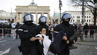 Police officers carry away a demonstrator after police stop a protest rally near the Brandenburg Gate