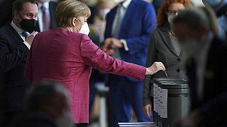 Angela Merkel dépose un bulletin dans une urne, lors d'une session parlementaire, Berlin, le 21 avril 2021