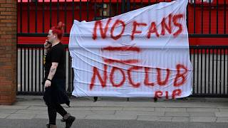 Banners critical of the European Super League project hang from the railings of Anfield stadium, Liverpool.