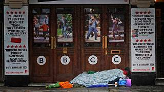 A rough sleeper rests at the entrance of theatre, closed due to the COVID-19 pandemic in London on Monday, February 8, 2021.