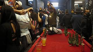 People wait to be frisked inside a bar during a civil police operation against illegal parties in Sao Paulo.