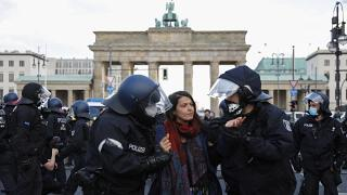 Police officers carry away a demonstrator after police stop a protest rally against the German government's policy to battle the corona virus pandemic.