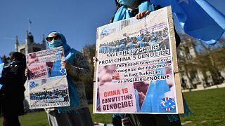 أفراد من مجتمع الأويغور يحملون لافتات أثناء تظاهرهم لدعوة البرلمان البريطاني للتصويت للاعتراف بالاضطهاد المزعوم لأقلية الأويغور المسلمة في الصين باعتباره إبادة جماعية