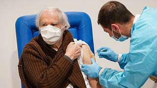 A health worker administers a dose of the Moderna COVID-19 vaccine to a man in his 80s at a vaccine center in Rome's Auditorium, Monday, Feb. 15, 2021.