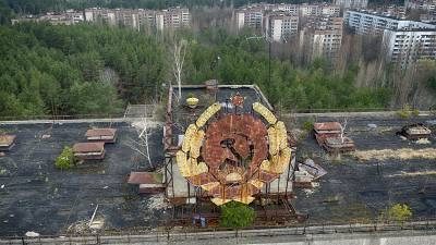 The rusty emblem of the Soviet Union is seen over the ghost town of Pripyat close to the Chernobyl nuclear plant, Ukraine, Thursday, April 15, 2021.