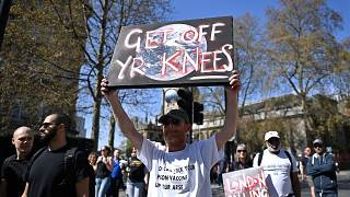 A man holds a placard aloft during anti-lockdown demonstrations in central London on Saturday