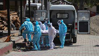عاملون في قطاع الصحة بالهند ينقلون جثة شخص توفي جراء إصابته بفيروس كورونا إلى المحرقة في إقليم جامو يوم الأحد 25 نيسان/أبريل 2021
