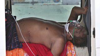"""Um """"doente covid"""" aguarda dentro de um veículo a admissão num hospital de Ahmedabad, Índia"""