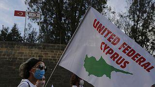 Kıbrıs'ın birleşmesi için düzenlenen gösteride elinde 'Birleşik Federal Kıbrıs' yazılı pankart taşıyan barış yanlısı bir aktivist