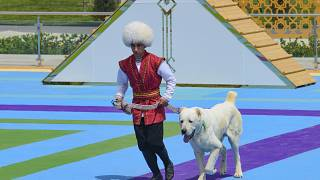 A man dressed in a national costume runs with his border guard shepherd dog Alabay during Dog Day celebration in Ashgabat, Turkmenistan, Sunday, April 25, 2021.