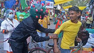 A man from a Non-governmental organization (NGO) wearing an outfit resembling the Covid-19 coronavirus moves around a marketplace urging people to follow the safety protocols