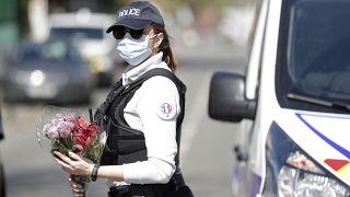 Une policière tient des fleurs que des habitants de Rambouillet lui ont donné, pour qu'il soit déposé sur les lieux de l'assassinat de Stéphanie Monfermé
