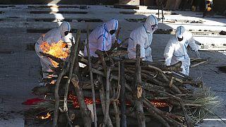 Familiares de uma vítima da Covid realizam rituais fúnebres antes da cremação