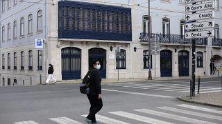 People wearing face masks walk across a street in Lisbon, Wednesday, Feb. 17, 2021.