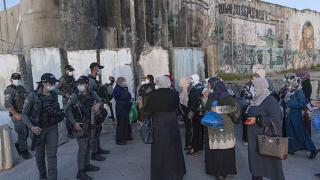 Palestinian women wait to cross the Qalandia checkpoint between the West Bank city of Ramallah and Jerusalem, during the the Muslim holy month of Ramadan, April 16, 2021.