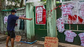 An anti-coup protester splashes red paint on student uniforms after they hanged them outside a school during a demonstration against the re-opening of the school by the junta