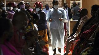 Numbers are handed out to people waiting to receive the AstraZeneca COVID-19 vaccine at Ndirande Health Centre in Blantyre Malawi on March 29, 2021.